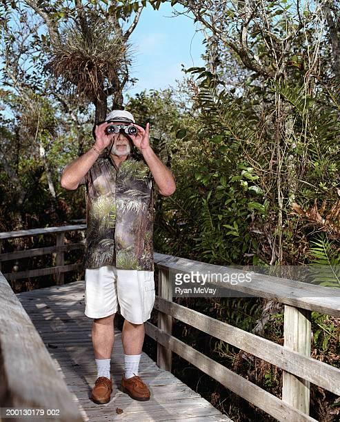 Senior man looking through binoculars on wooden walkway