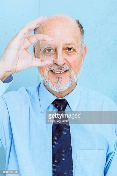 Senior man looking through lens