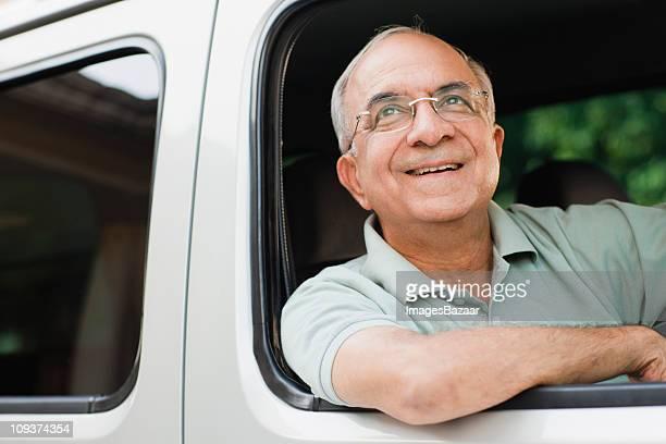 Senior man looking up in vehicle