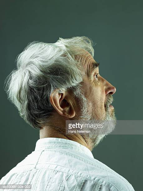 Senior man looking up, studio profile