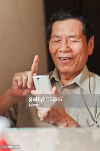 Senior man looks at smart phone : Stock Photo