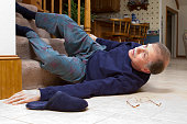 An adult male senior, laying on his back, struggles to get up after falling down a flight of stairs in his home. His slipper and glasses lay beside him on the tile floor.