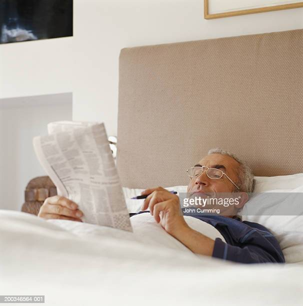 Senior man lying in bed holding newspaper and pen