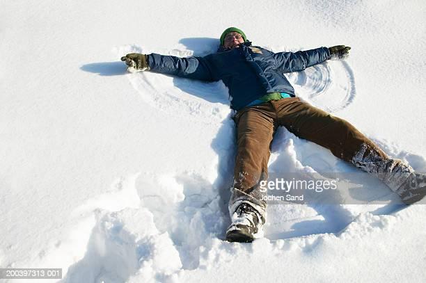 Alter Mann liegen im Schnee machen Schnee-Engel, Lächeln