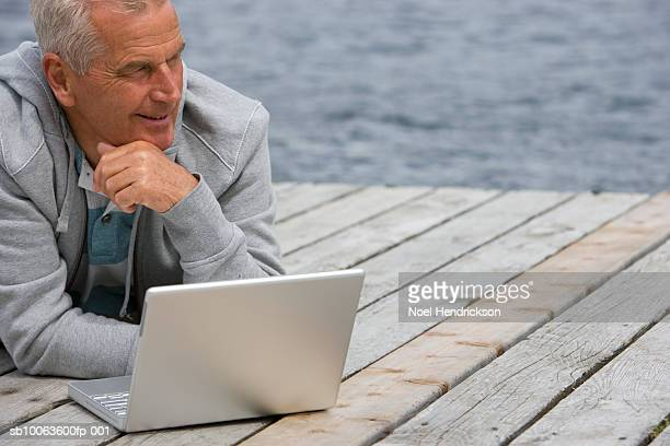 Senior man lying on pier in front of laptop, hand on chin, close-up