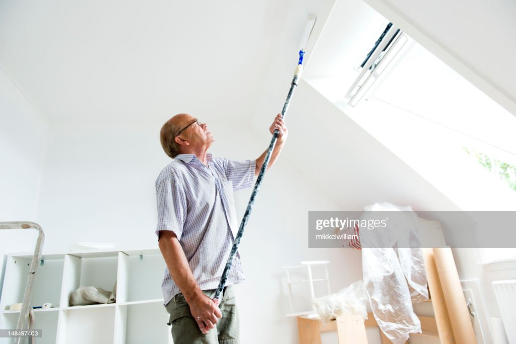 Senior man makes home improvement with new paint : Stock Photo