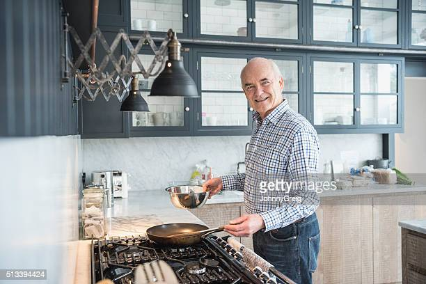 Senior man making dinner and smiling to camera in kitchen