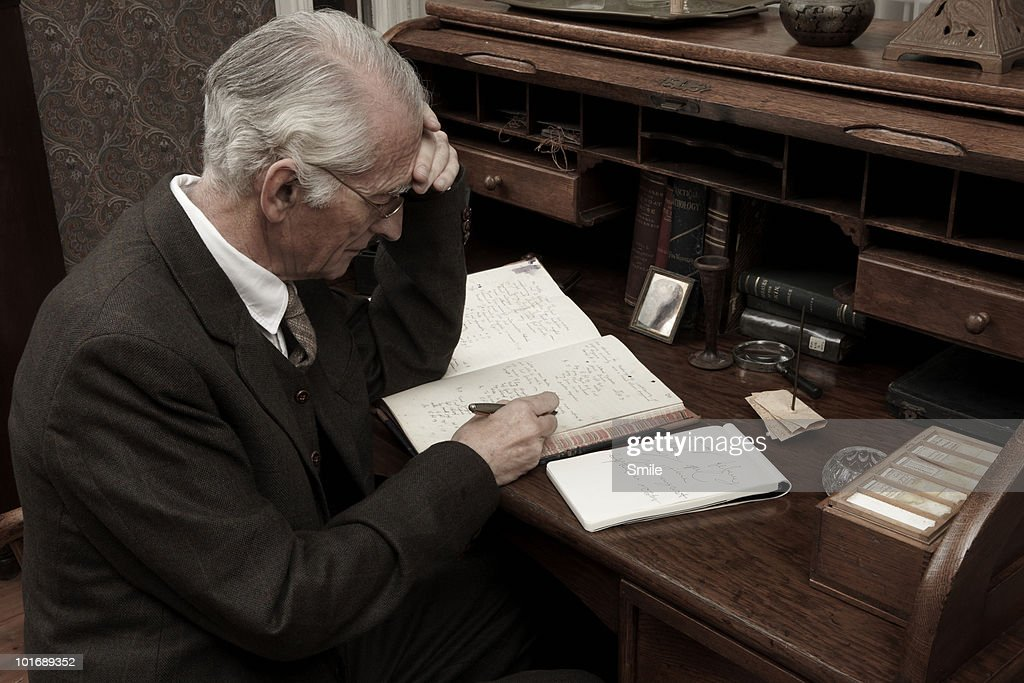 Senior man making notes at desk : Stock Photo
