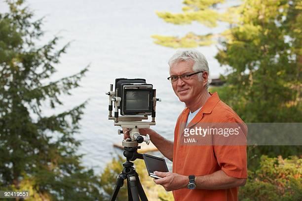 Senior Man Making Portraits With Analogue Camera