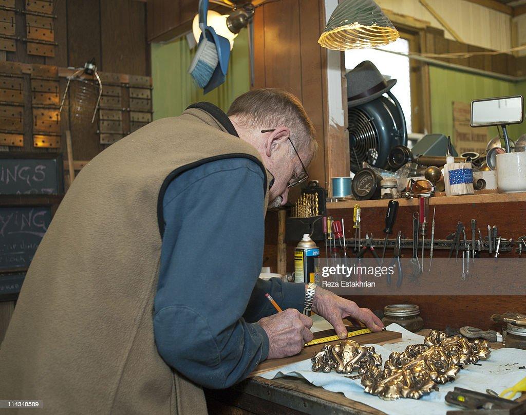 Senior man measures wood panel : Stock Photo