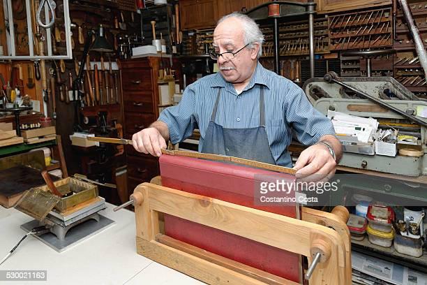 Senior man measuring book spine in traditional bookbinding workshop