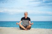 Senior man meditating on the beach, summer vacation workout