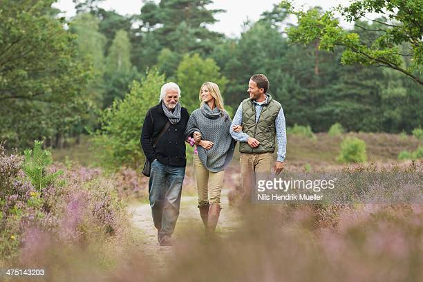 Senior man, mid adult man and woman walking through forest