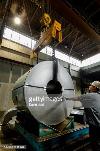 Senior man moving coiled steel with crane, side view : Stock Photo