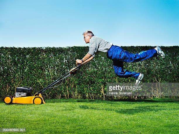 Senior man mowing lawn, jumping, side view