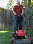senior man mowing lawn, copy space
