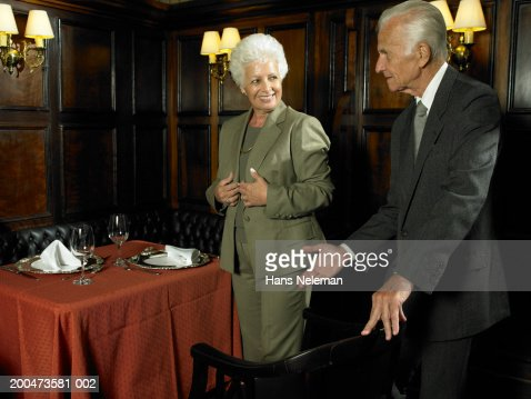 Senior man offering seat to wife in restaurant