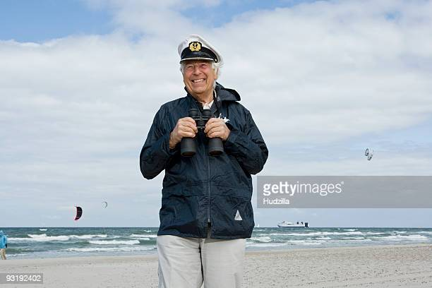 A senior man on a beach holding binoculars