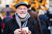 Happy senior man on an outdoor Christmas market, holding enameled cup. Winter time.