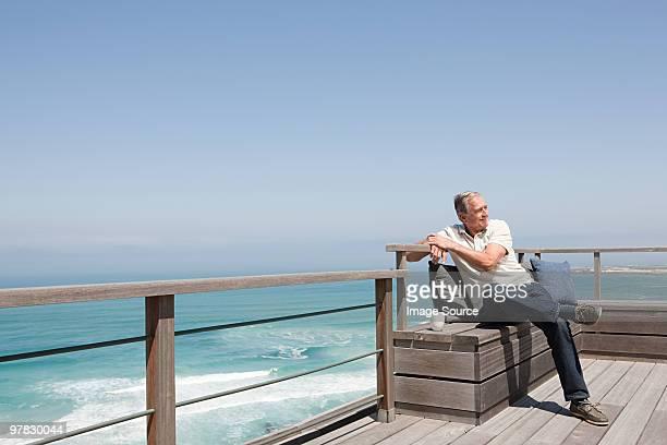 Senior man on balcony by the sea