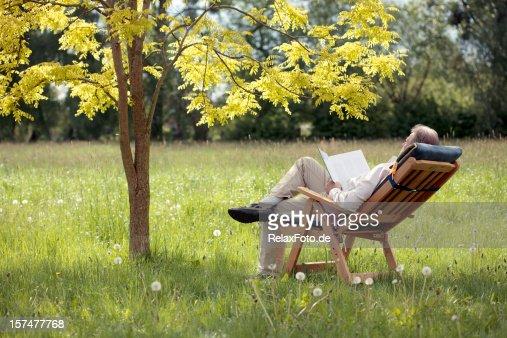 Senior Man on deck chair under tree reading book (XXXL)