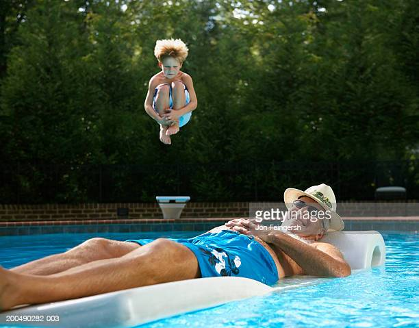 Senior man on float in pool, boy (5-7) jumping in