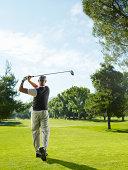 Senior man on golf course swinging, rear view