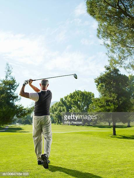Senior man on golf course swinging, rear view