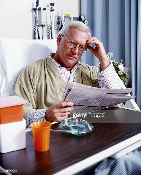 Senior man on hospital bed reading newspaper