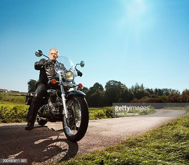 Senior man on motorbike, parked across road, portrait, low angle view