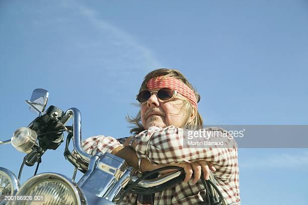 Senior man on motorbike, wearing sunglasses, low angle view