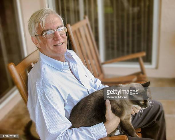 Senior Man on porch with cat in lap