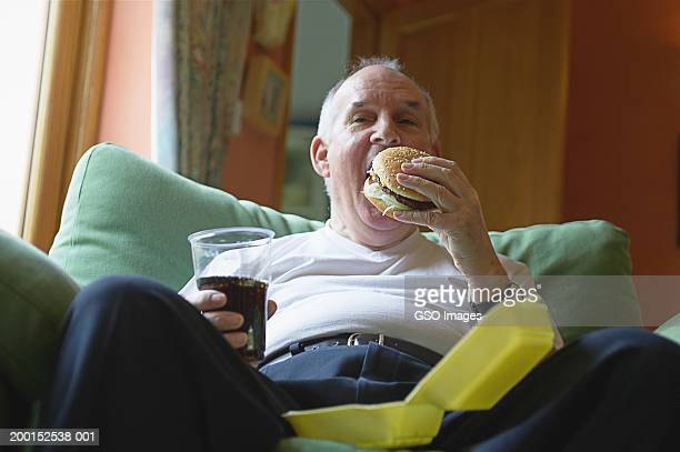 Senior man on sofa, eating hamburger