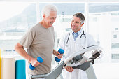 Senior man on treadmill with therapist in fitness studio