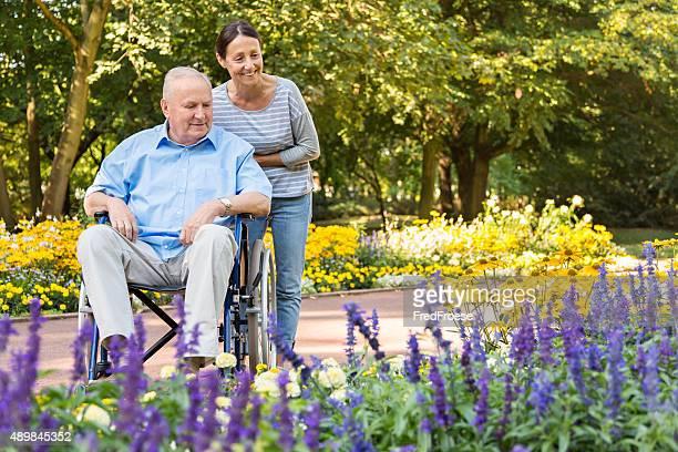 Alter Mann auf Rollstuhl mit Altenpfleger im Freien