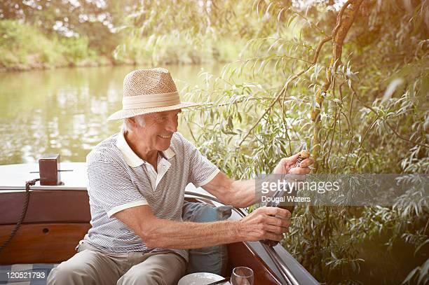 Senior man opening bottle of drink on boat.