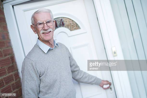 Senior man opening door to his house