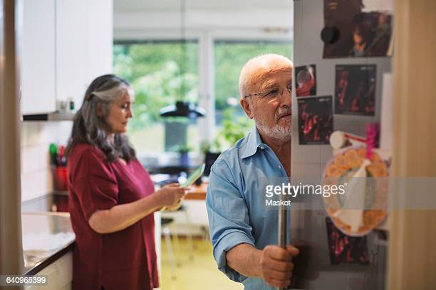 Senior man opening refrigerator while woman using digital tablet at home