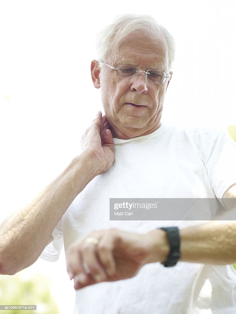 Senior man outdoors, looking at wristwatch and checking pulse, low angle view