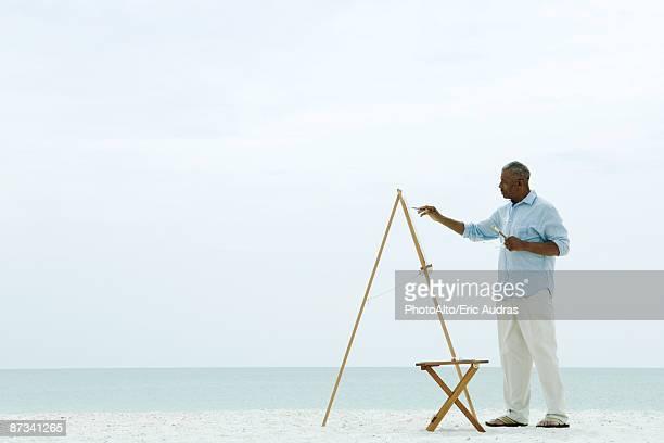 Senior man painting canvas beach, side view