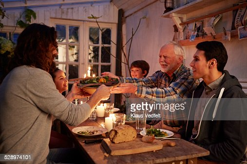 Senior man passing bowl of salad to son