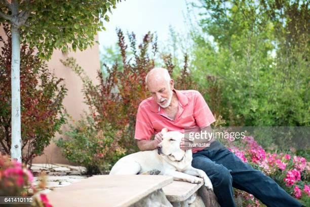 Senior man petting dog outdoors