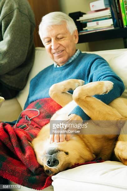 Senior man petting his dog on sofa