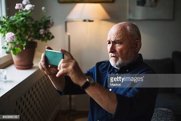 Senior man photographing through mobile phone at home