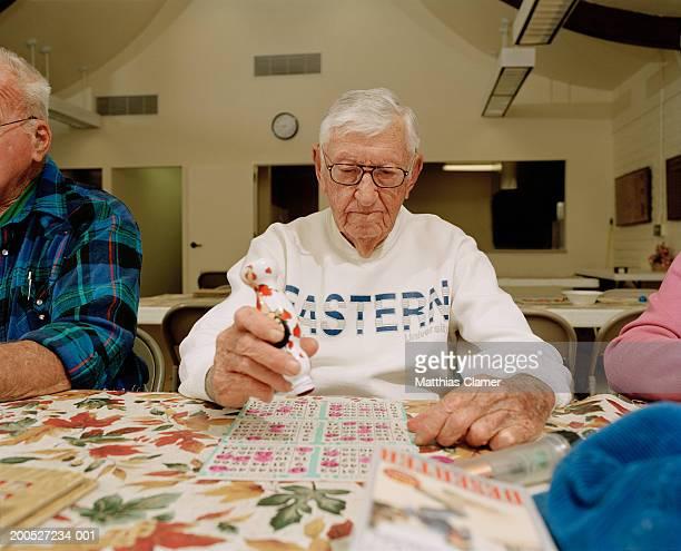 Senior man playing bingo, sitting by table