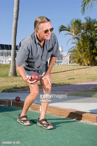 Senior man playing bocce ball on lawn, close-up