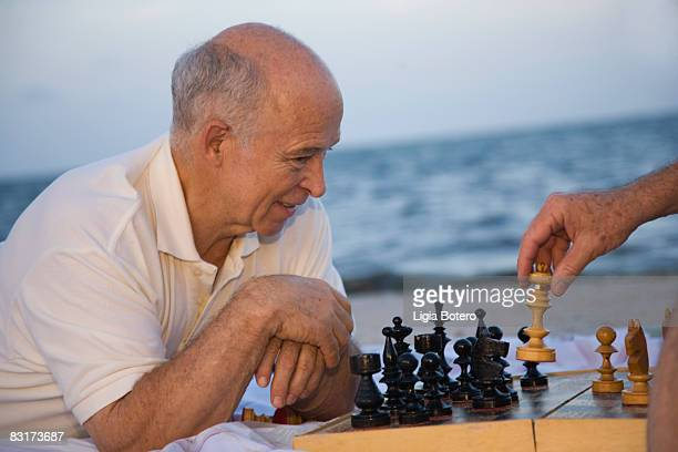 Senior man playing chess at the beach