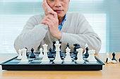 Asian senior man playing chess.
