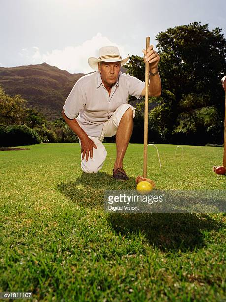 Senior Man Playing Croquet Kneeling Holding a Croquet Mallet