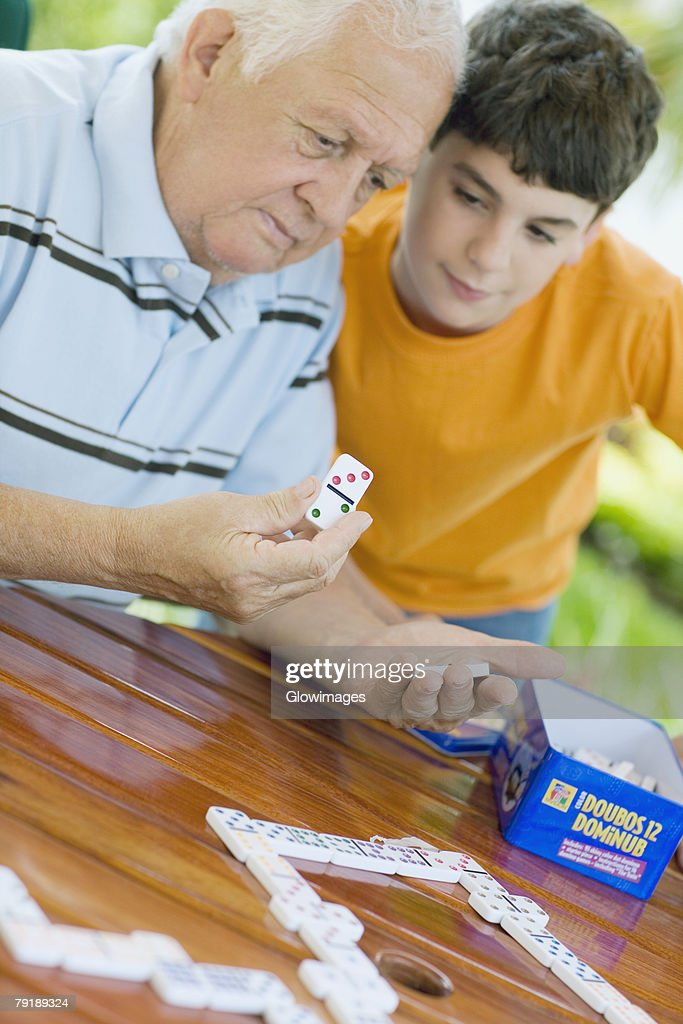 Senior man playing domino with his grandson : Stock Photo